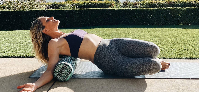 Structural alignment expert Lauren Roxburgh foam rolling on a yoga mat outdoors