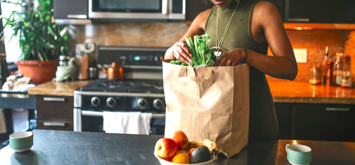 Woman unpacking her grocery bag of the fruits and vegetables