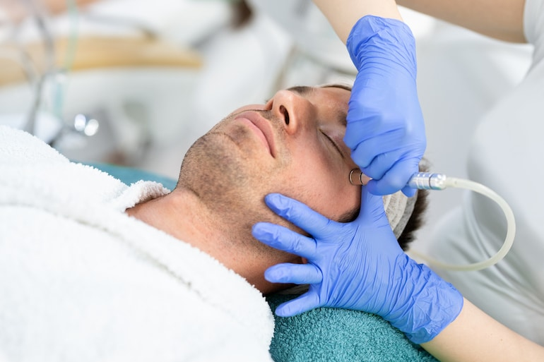 Facialist performing exfoliating microdermabrasion treatment on a young man