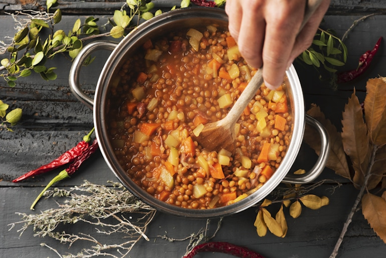 Man mixing a plant-based lentil stew for plant protein and other nutrients