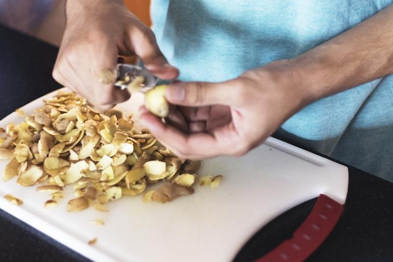 Man peeling potatoes, one of the longest-lasting produce items