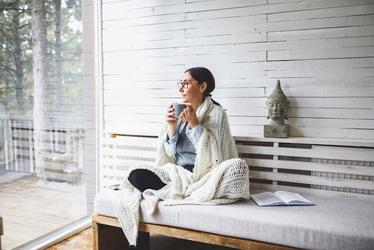 Woman sitting in her cozy reading nook drinking tea and looking out the window