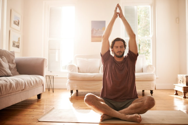 Man meditating on yoga mat in his home, which he turned into a calming social distancing sanctuary