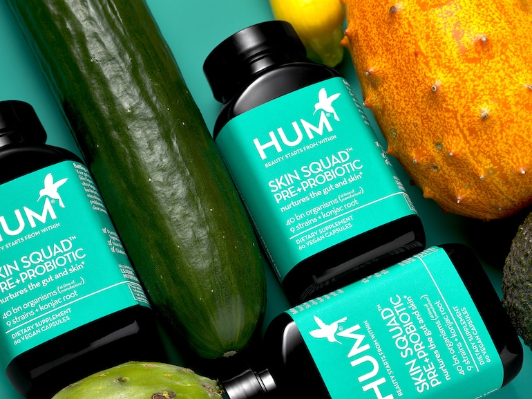 HUM Skin Squad Pre and Probiotic for clear skin, next to cucumber and other raw ingredients
