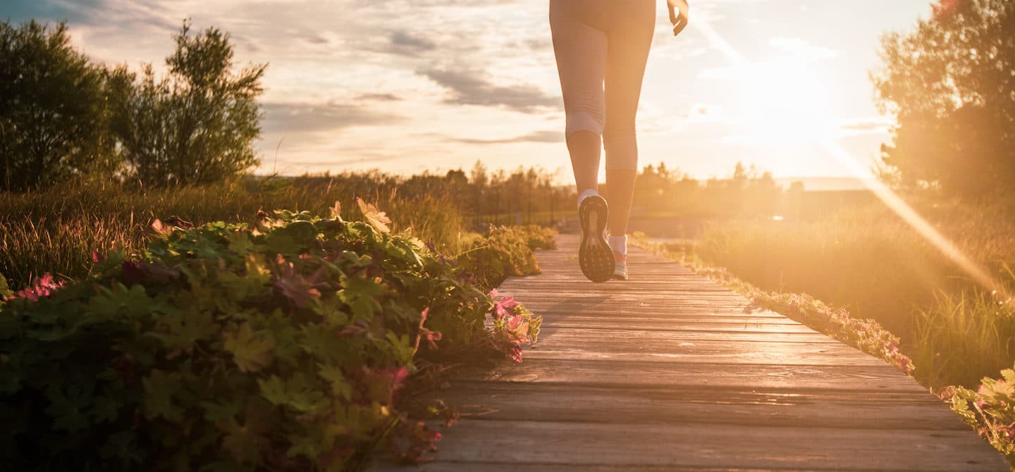 Woman walking on a wooden path in nature before dusk to reap the surprising benefits of walking daily