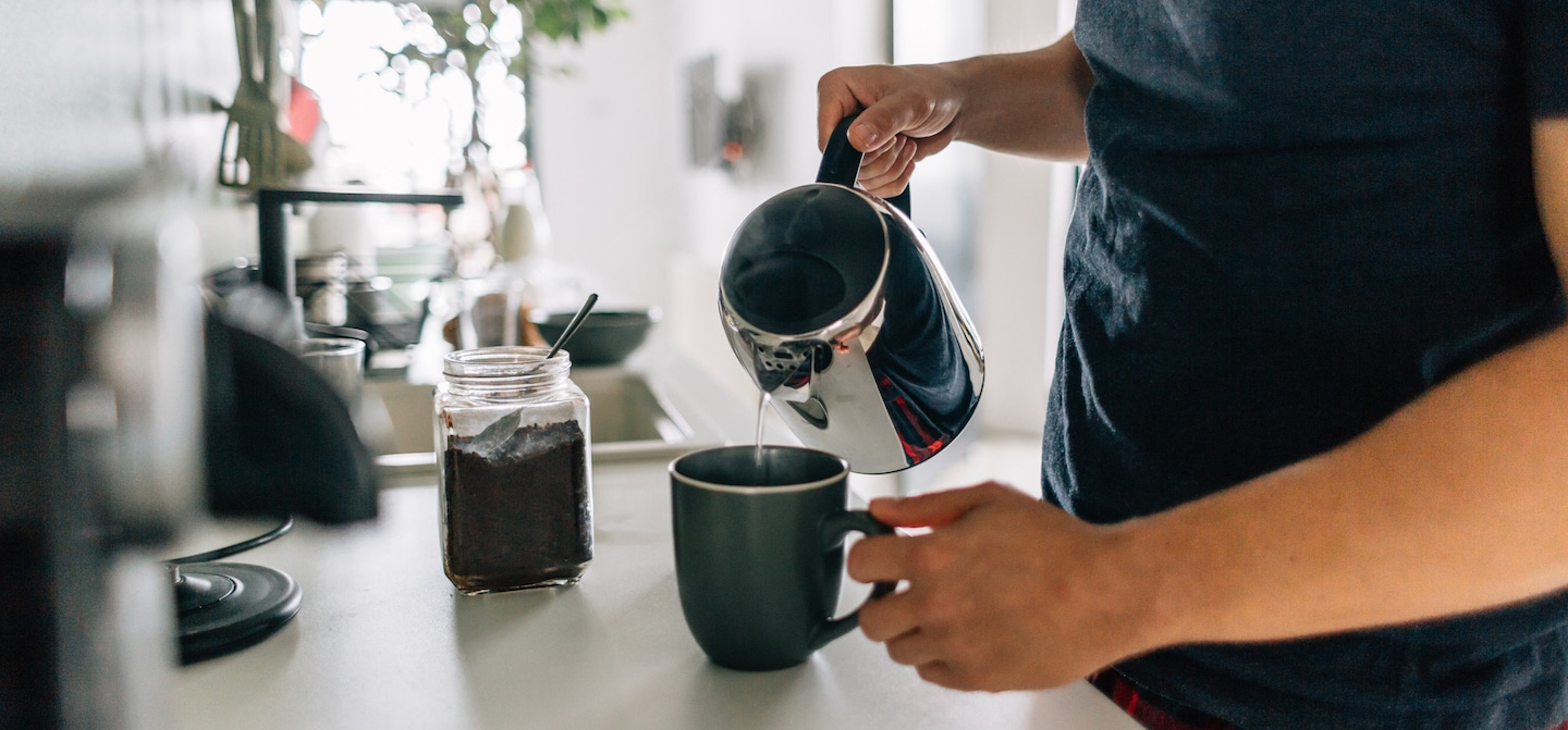 Man pouring coffee at home, but too much caffeine can weaken immune function