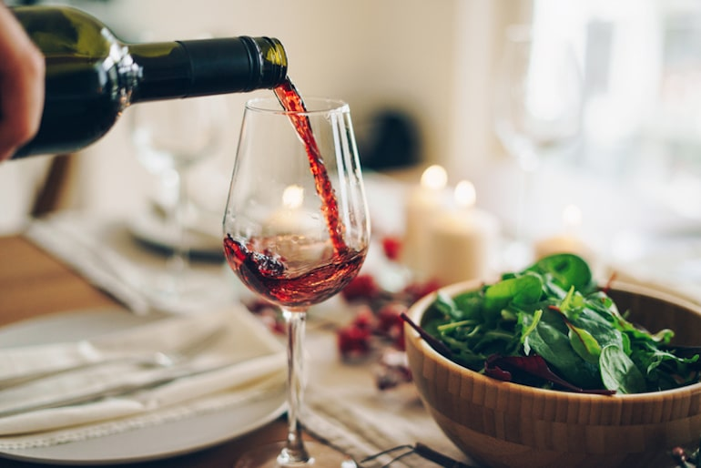 Person pouring red wine in glass at home to take the edge off, but is a bad dietary habit that can negatively impact the immune system