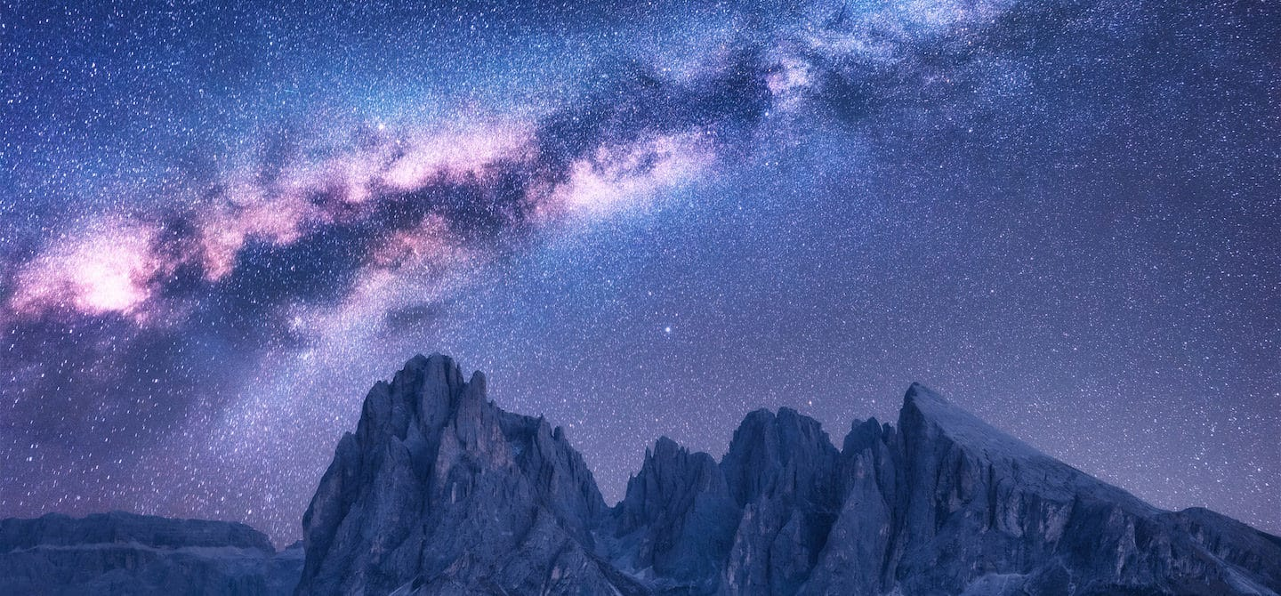 Purple and blue starry night sky above mountains