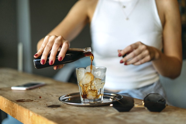 Woman pouring highly caffeinated cold brew over ice