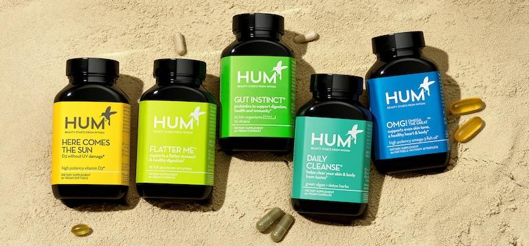 Botellas de suplementos de HUM Nutrition en la arena para ilustrar nuestra transición a plásticos 100% oceánicos