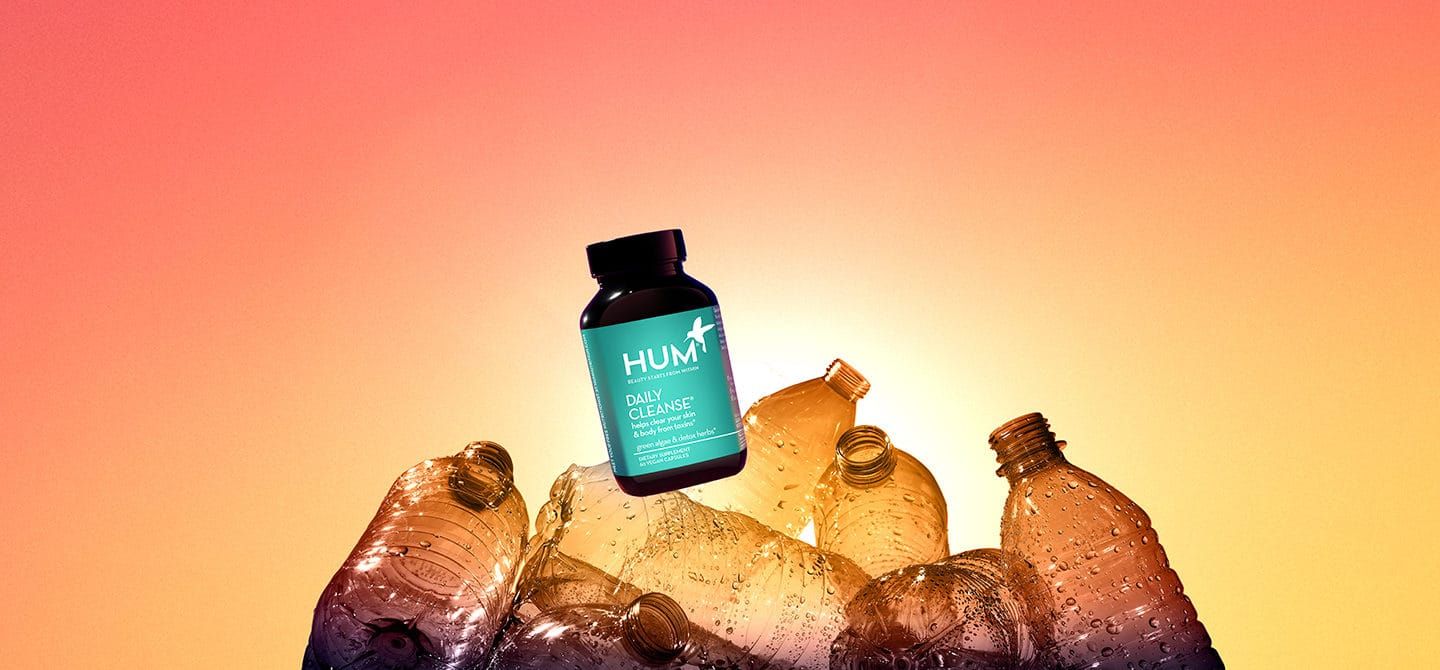 HUM Daily Cleanse supplement on top of empty plastic bottles to demonstrate HUM's transition to 100% ocean-bound plastic