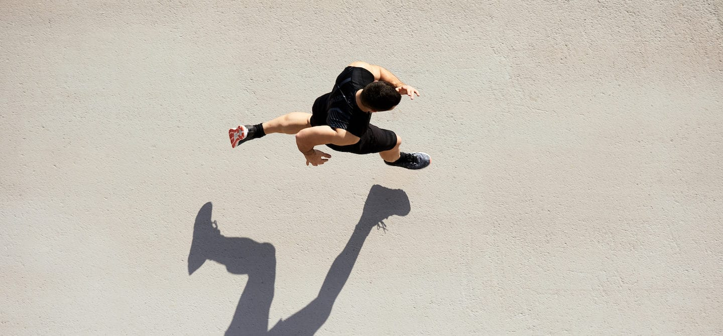 Overhead shot of man running with shadow, supported by boosting his levels of nitric oxide for respiratory health
