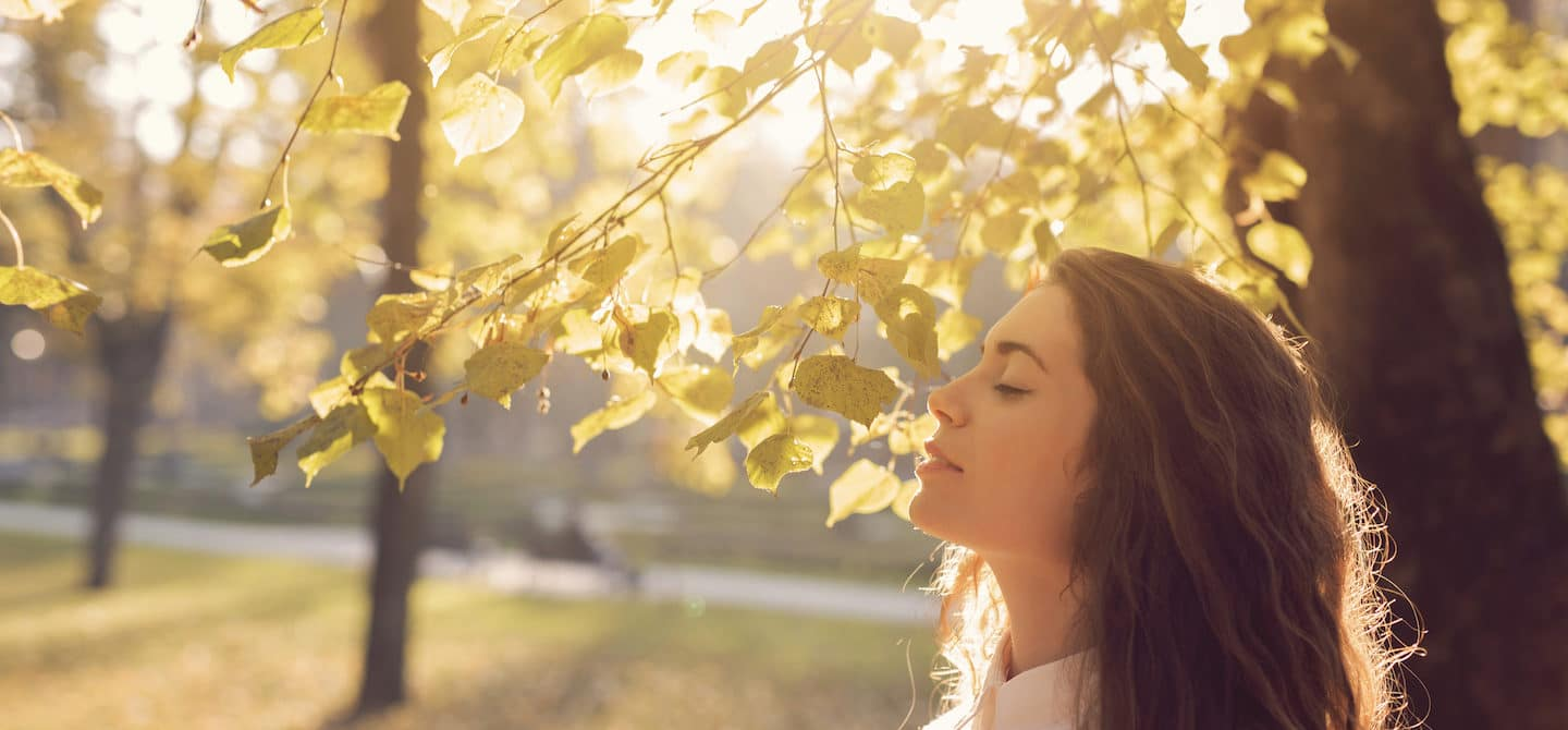 Woman at park under trees in sunlight to get immunity-boosting vitamin D