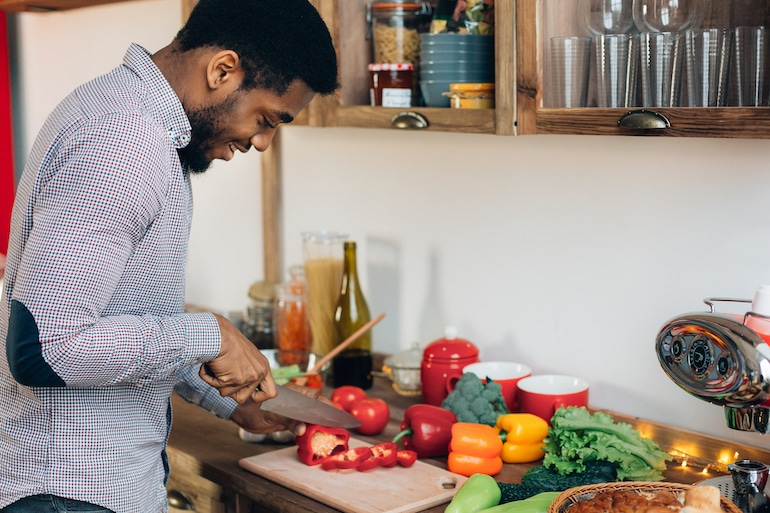 Man cutting bell peppers and other produce in kitchen to prepare to freeze