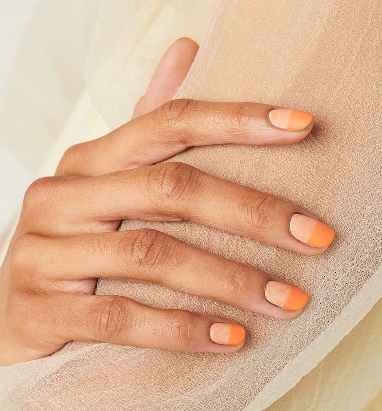 Woman with two-toned orange gel nails