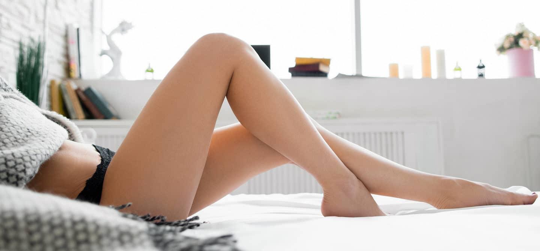 Woman's legs bent on bed, wearing lacy underwear