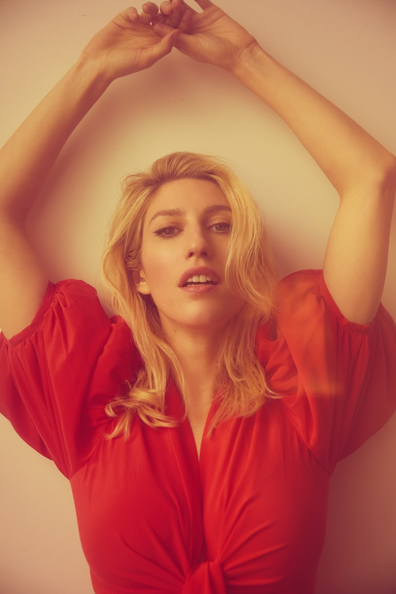 Vogue sex writer Karley Sciortino of Slutever with arms above head in red pouffy dress, discussing her journey toward vaginal health