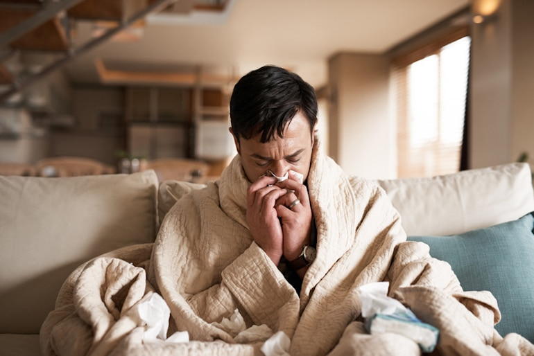Man blowing nose under covers on couch, who needs vitamin D for immune support