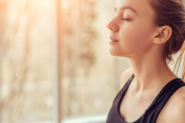 Young woman doing breathing exercises for healthy lungs