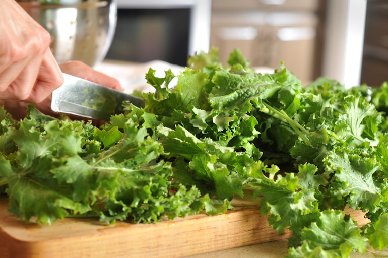 Woman chopping kale to put into a vitamin C smoothie for an immune booster
