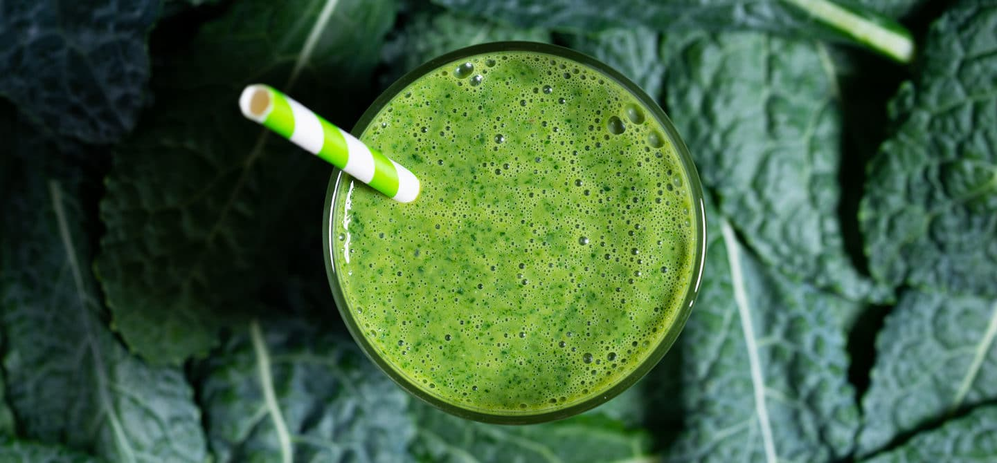 Kale and vitamin C smoothie on a bed of kale leaves