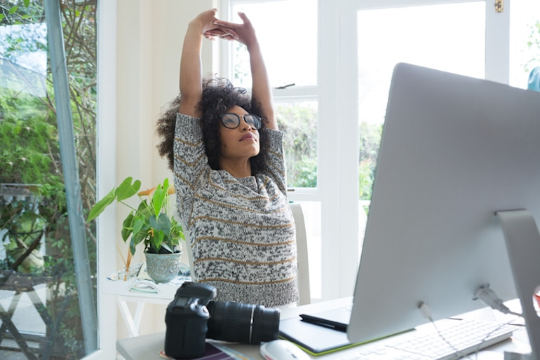 Woman doing overhead stretches at her desk