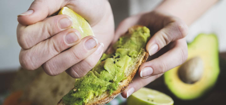 Woman squeezing a lemon onto avocado toast