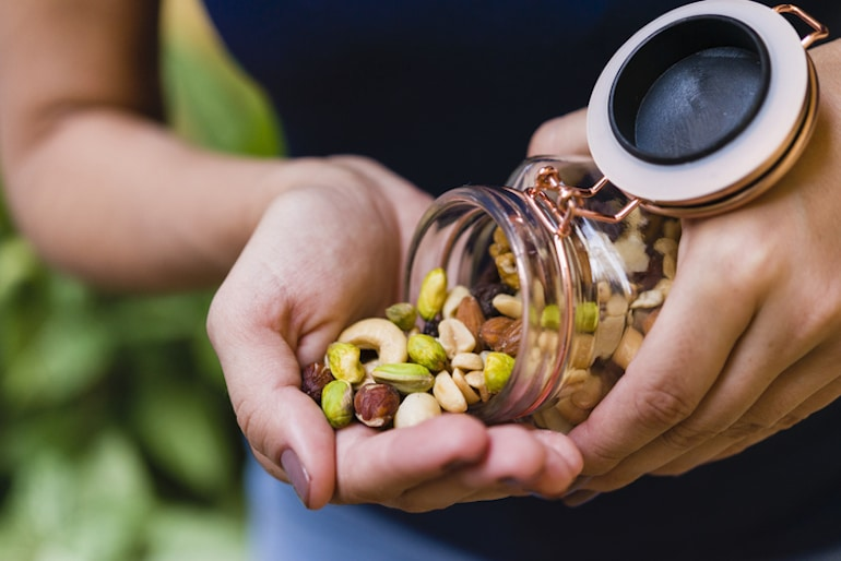 Woman pouring assorted nuts from glass container, which are rich in magnesium to help relieve constipation
