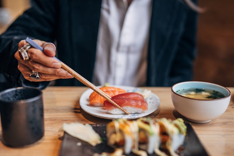 Man eating sushi with fatty fish in restaurant