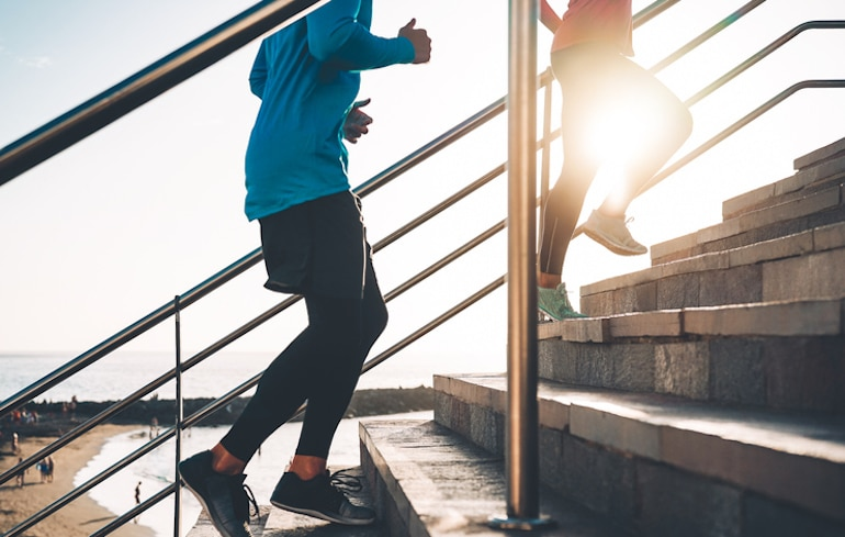 Man and woman running up the steps, a natural way to relieve constipation is through movement