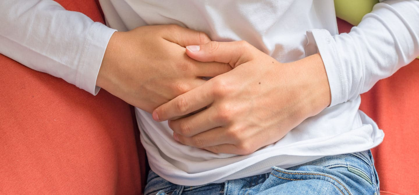 Man feeling unwell on couch touching his stomach to emphasize connection between gut health and immune system