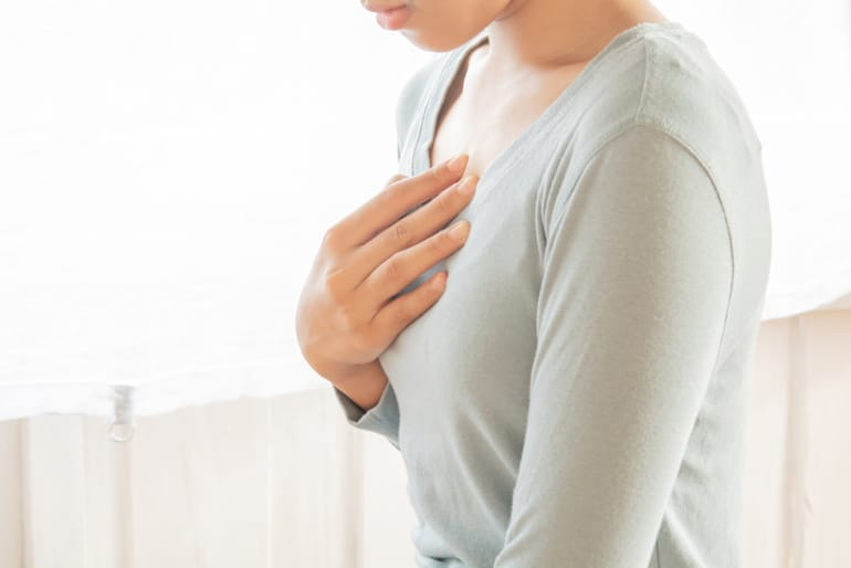 Woman clutching her chest in pain from heartburn