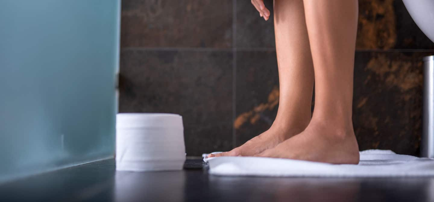 Woman sitting on toilet next to a roll of toilet paper