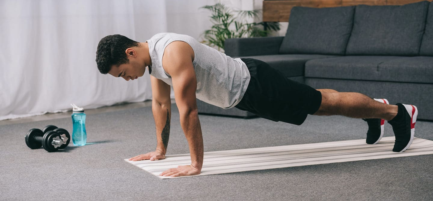 Man in plank pose on a yoga mat at home