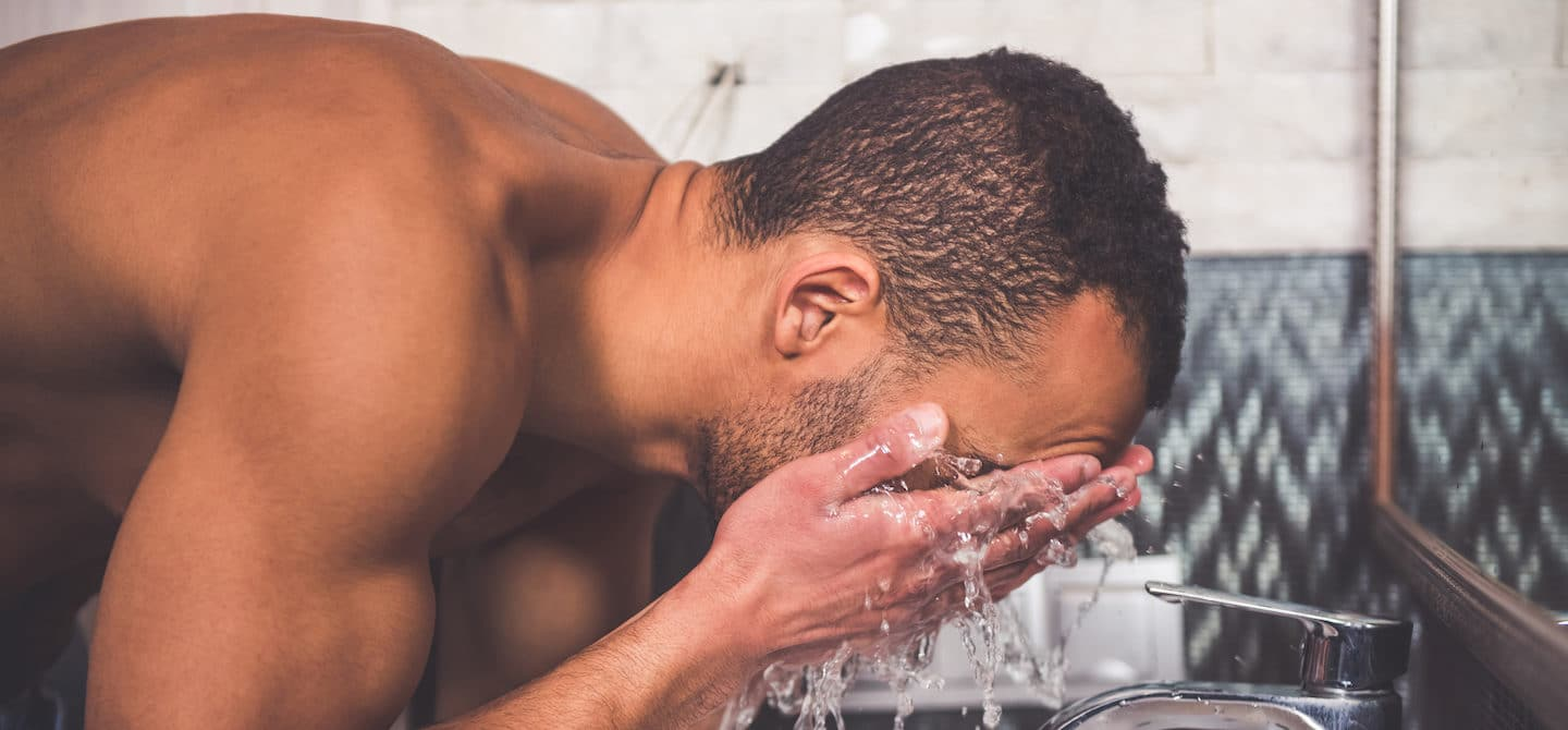 Man washing his face as the first step of his men's skincare routine