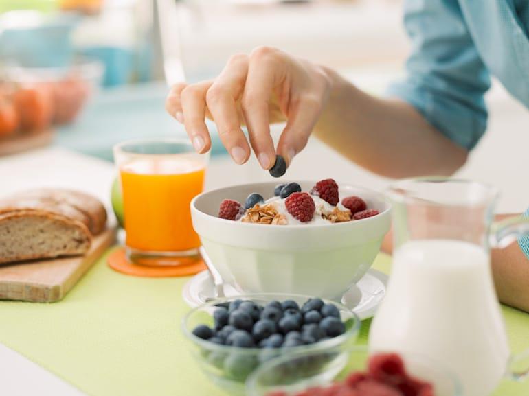 Woman eating mixed berries on Greek yogurt for breakfast