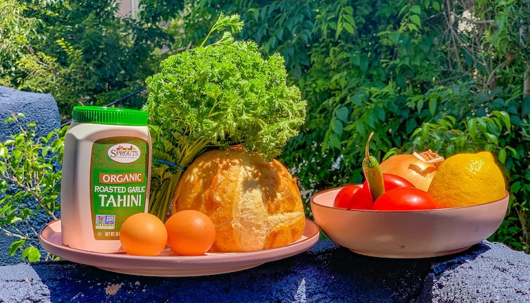 Ingredients for a traditional shakshuka recipe including onion, tomato, parsley, eggs, bread, and tahini paste