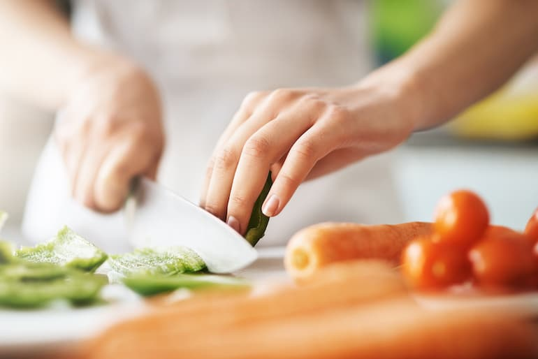 Woman chopping vegetables with knife at an angle