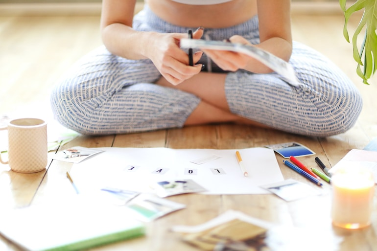 Woman getting crafty to make her vision board to harness positive thinking and the power of visualization