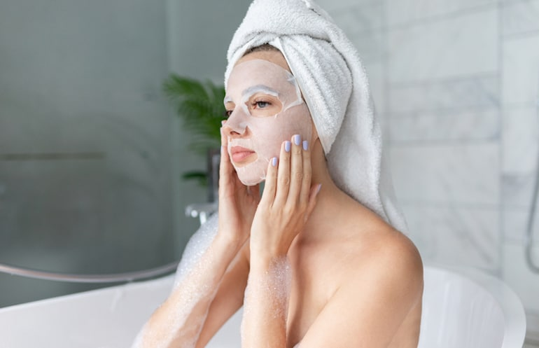 Woman in bath wearing a sheet mask, one of the most popular parts of the best K-beauty routine