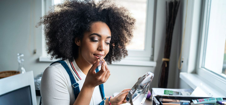 Woman applying makeup at home