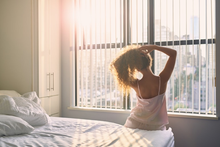Woman sitting up and stretching in bed in the morning looking out the window
