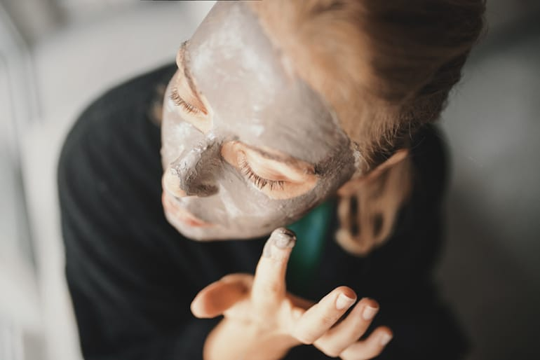 Woman applying a clay mask, one of the best tips for clear skin and treating blackheads