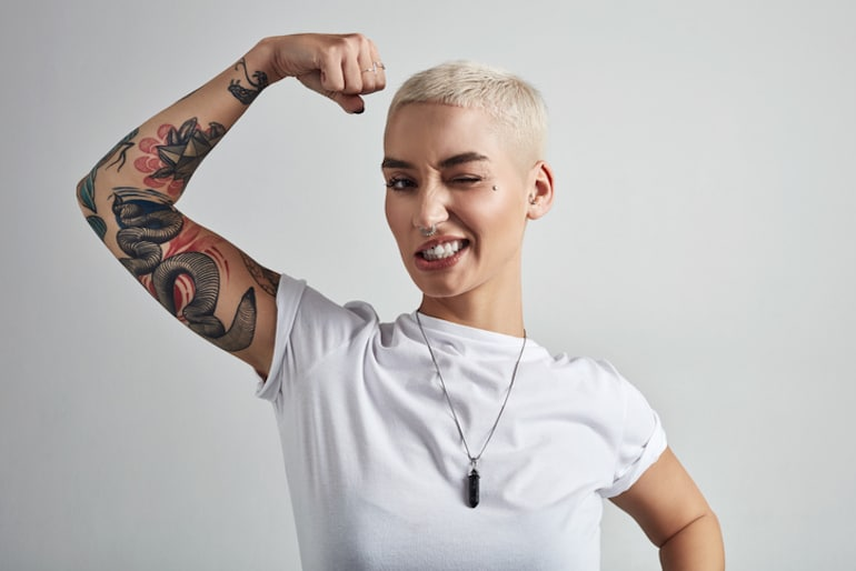 Woman flexing her biceps and winking, showing off her confidence after practicing the best self-love tips guided by Anna Sweeney