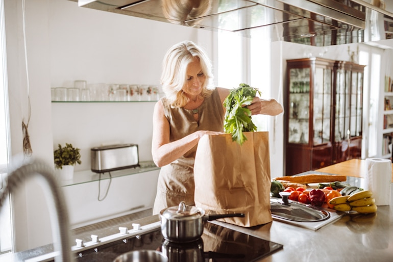 Middle-aged woman unpacking fresh fruit and vegetables for her Galveston Diet plan for weight loss and menopause