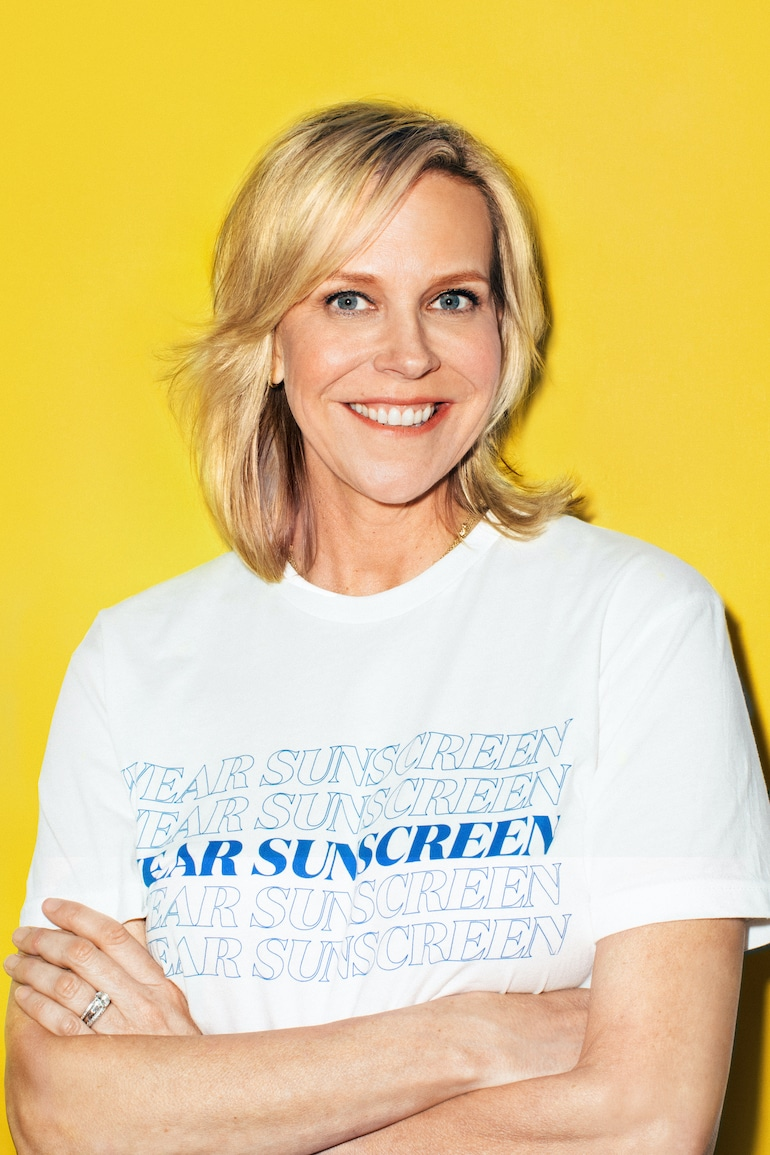 "Supergoop! Founder Holly Thaggard in front of yellow background wearing shirt that says ""wear sunscreen"""