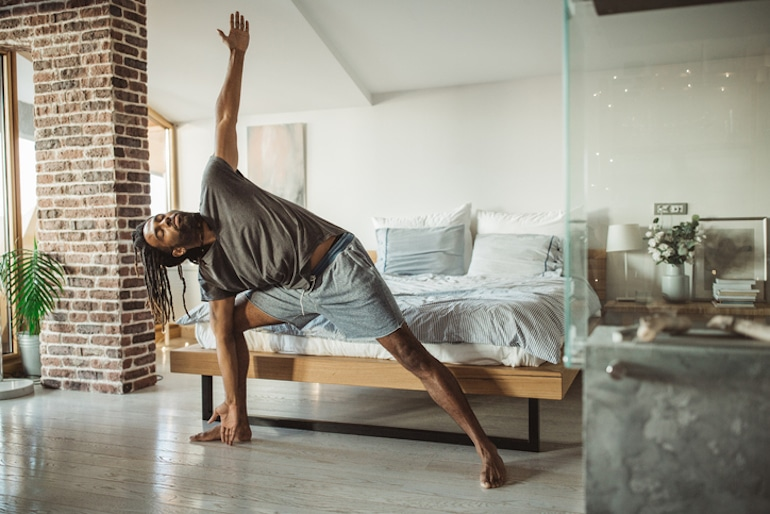 Man in yoga triangle pose for positive time alone to help balance work and life