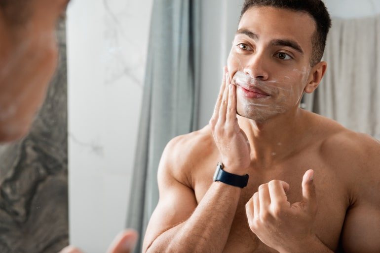 Man moisturizing his skin in the mirror to prevent breakouts and promote clear skin