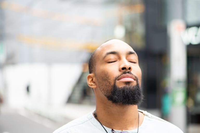 Man with eyes closed outdoors, positive and hopeful with the power of visualization