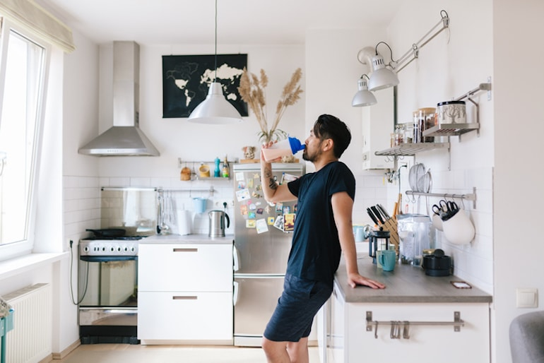Man drinking a protein shake in his kitchen after a workout to balance blood sugar and avoid cravings